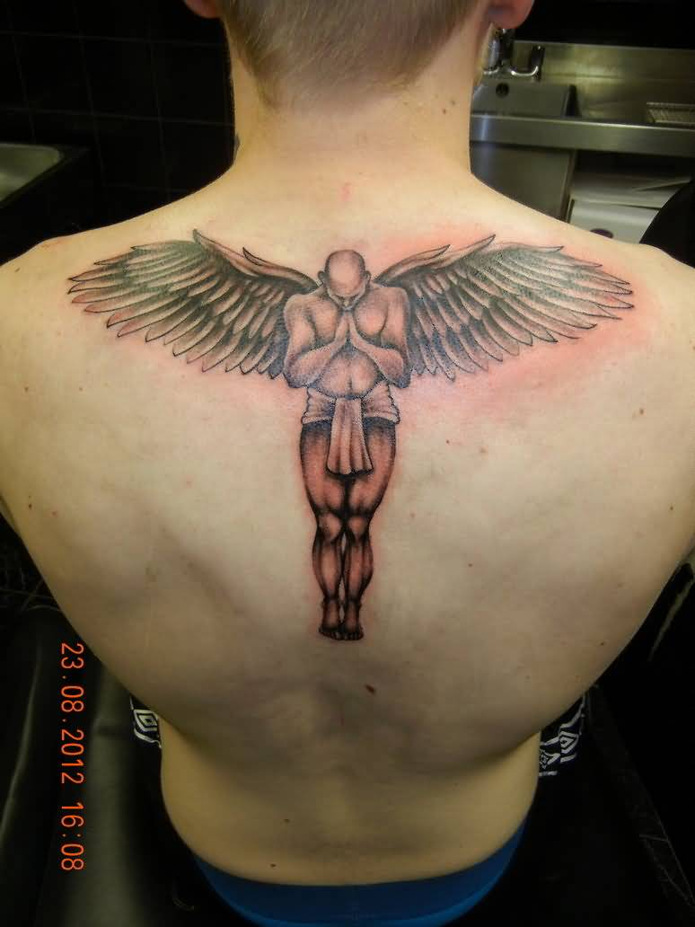 men shows praying angel and angel wings tattoo on upper back. Black Bedroom Furniture Sets. Home Design Ideas