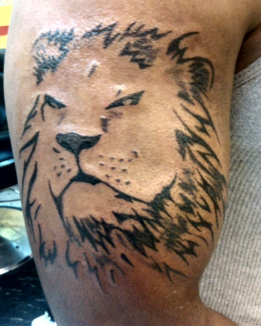 Black Ink Aggressive Lion Tattoo On Men's Bicep