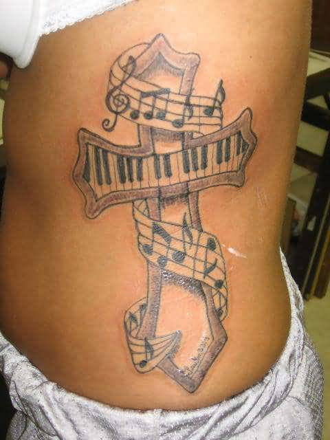 Mind Blowing Cross And Musical Symbols With Keyboard Tattoo On Women's rib Side