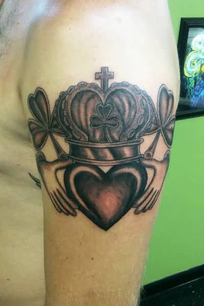 Outstanding Small Cross And Claddagh Tattoo On Men's Upper Sleeve