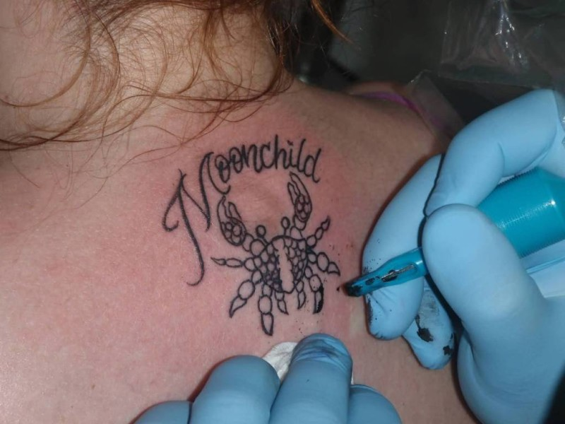 Tattoo Artist Make Simple Small Crab And Moonchild Word Tattoo On Upper Back