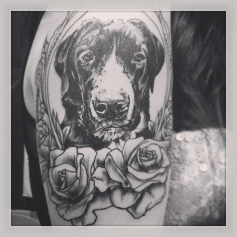 Nice Looking Dog Face In Mirror And Lovely Flowers Tattoo Design Make On Upper Sleeve