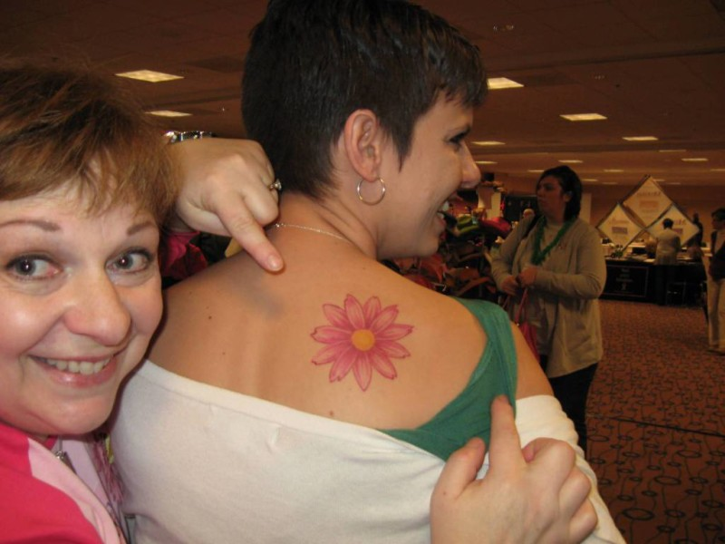 Smiling Stylish Women Show Fabulous Colorful Daisy Flower Tattoo On Upper Back
