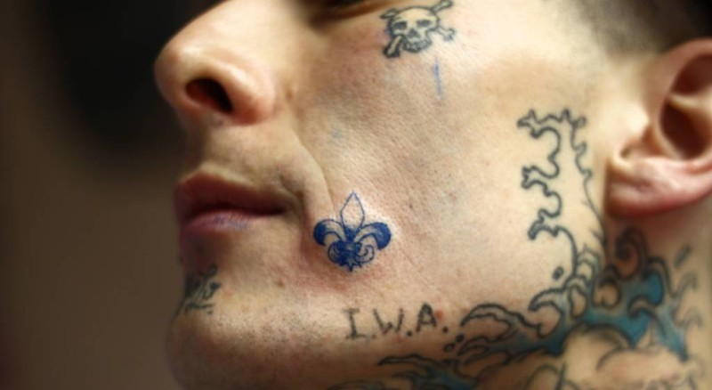 Men Show Amazing Very Small Fleur De Lis Tattoo On Face