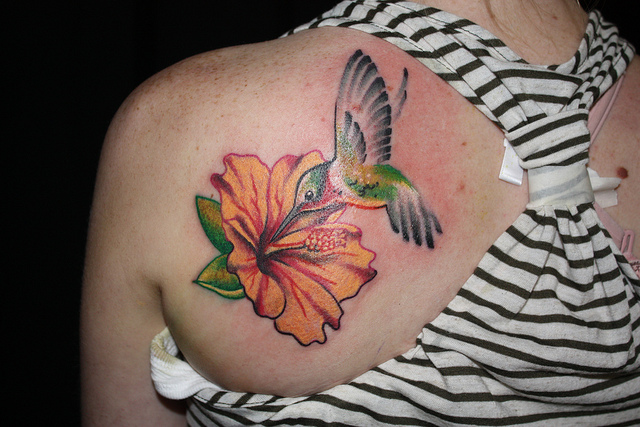 Pretty Hot Women Show Nice One Simple  Hummingbird With Orange Flower Tattoo