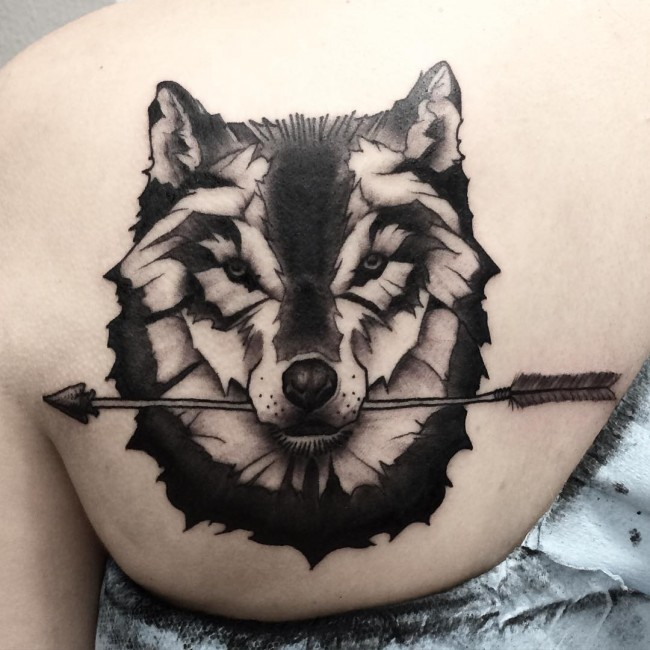 Angry Wolf Hold Arrow Tattoo On Girl Back