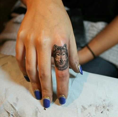 Small And Cool Wolf Face Tattoo On Girl Finger